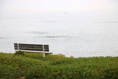 Wietrzejąca drewniana ławka przegapia ocean Zdjęcie Stock