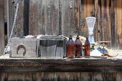 Wietrzejąca plenerowa ławka z drewnianymi pudełkami i szklanymi butelkami Zdjęcia Royalty Free