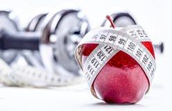 Świeży czerwony jabłko, taśmy miara w tło sprawności fizycznej dumbbells, i Fotografia Stock