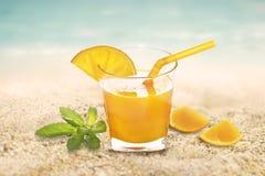 Świeży sok pomarańczowy z mennicą w szkle na piaska morza plaży letnim dniu Obrazy Stock