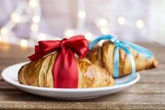 Świezi croissants z czerwonym faborkiem i błękitnym faborkiem na bokeh tle Fotografia Stock