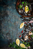 Świezi czarni mussels w drewnianym pucharze z cytryną i składnikami dla gotować na ciemnym nieociosanym tle, odgórny widok, borde Fotografia Royalty Free