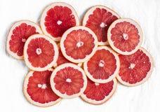 Świezi grapefruitowi plasterki na lekkim tle, odgórny widok Zdjęcie Stock