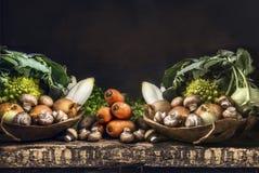 Świezi organicznie warzywa od ogródu na starym nieociosanym drewnianym stole, jarski kucharstwo Zdjęcia Royalty Free