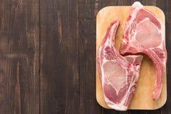 Świezi wieprzowina kotleciki lub cutlets na drewnianym tle Obraz Stock