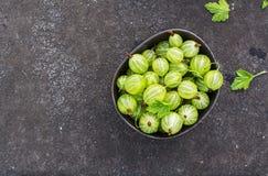 Świezi zieleni agresty w ceramicznym pucharze na ciemnym tle Odgórny widok Obraz Royalty Free