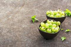 Świezi zieleni agresty w ceramicznym pucharze na ciemnym tle Odgórny widok Zdjęcia Stock