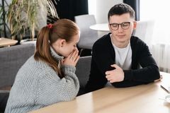 Wife asking for forgiveness to her husband after conflict sitting in the cafe royalty free stock photography