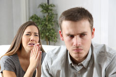 Wife asking for forgiveness to her husband. Wife asking for forgiveness to her ex husband after conflict sitting on a couch in the living room of a house stock photography