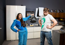 Wife asking her husband to take out the trash. In the kitchen Stock Image