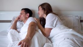 Wife asks forgiveness from her husband. She talks kindly to him and apologizes lying in bed in the evening stock footage