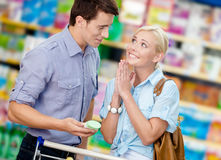 Wife asks husband to buy cosmetics for her Stock Photography