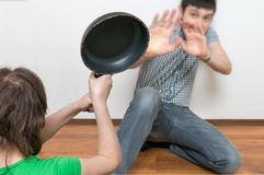 Wife is attacking her husband with a frying pan. Domestic violen Royalty Free Stock Photography