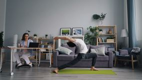 Wife is working with laptop at table while sporty husband exercising doing yoga. Wife attractive young woman is working with laptop at table while sporty husband stock footage