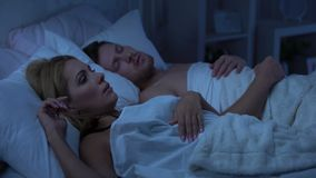Wife in bed with husband, sleepless because of snoring, nasal septum deviation