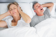 Wife blocking her ears from noise of husband snoring. In bedroom at home royalty free stock photo