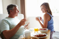 Wife Bringing Husband Breakfast In Bed On Tray. Smiling At Each Other Royalty Free Stock Images