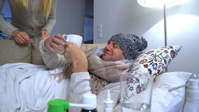 Wife Brings Her Sick Husband A Mug With A Hot Drink. stock footage
