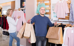 Wife buying dress at apparel store, man is bored Stock Photos