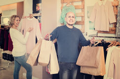 Wife buying dress at apparel store, man is bored Royalty Free Stock Images