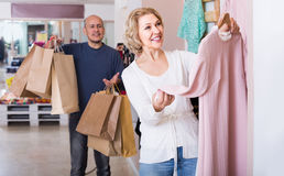 Wife buying dress at apparel store, man is bored Stock Photo