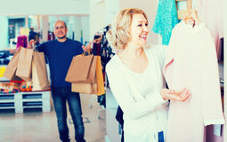 Wife buying dress at apparel store, man is bored Royalty Free Stock Photos