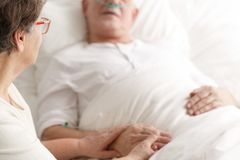 Wife caring about dying spouse. Loving wife caring about dying ill spouse before his death stock photo