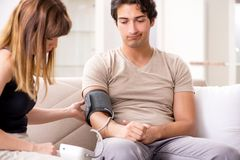 Wife checking husband`s blood pressure royalty free stock photos