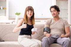 Wife checking husband`s blood pressure royalty free stock image