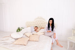 Wife checks meanly her husband`s phone, while he sleeps Royalty Free Stock Image