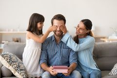 Wife and child making surprise to dad on fathers day. Loving wife and kid daughter making surprise to smiling dad receiving gift on fathers day, family closing royalty free stock photography