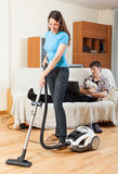 Wife cleaning and husband rests Royalty Free Stock Image