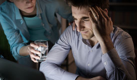 Wife comforting her husband. Wife comforting her depressed husband and giving him a glass of water, he is having an headache and feeling sick Royalty Free Stock Image