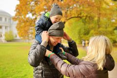 Wife corrects clothes for husband with child on a shoulders in park Royalty Free Stock Images