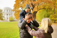 Wife corrects clothes for husband with child on a shoulders in park Royalty Free Stock Image