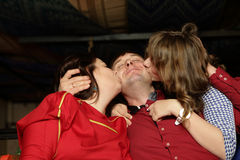 Wife and daughter kissing their husband and father Royalty Free Stock Image