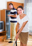 Wife doing vacuuming clean-up in living room Stock Photos