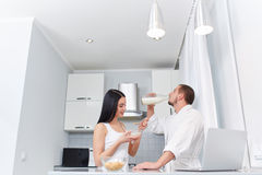Wife eating porridge and husband drinking milk. View of couple having breakfast together. Pretty brunette eating oat flakes and her husband drinking milk. Woman Stock Photography