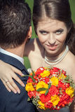 Wife embracing her husband with bouquet in hands Royalty Free Stock Photos