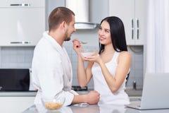 Wife feeding her husband of oat flakes. Stock Image