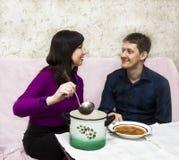 Wife feeds husband Stock Image