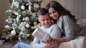Wife gently hugs her husband at home, gift for beloved woman on eve of new year. Wife gently hugs her husband at home, gift for beloved woman on the eve of new stock video