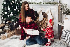 Mother giving present to her husband while baby looking at them. royalty free stock image