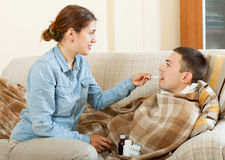 Wife giving  cough syrup to her husband Stock Photography
