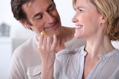 Wife giving husband a biscuit. Playful wife giving husband a biscuit Royalty Free Stock Image
