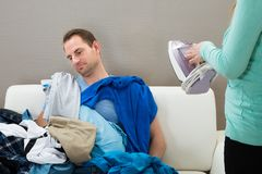 Wife giving ironing work to husband Royalty Free Stock Photography