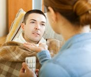 Wife giving pills to diseased man royalty free stock photo