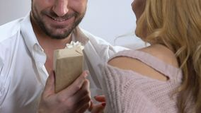 Wife giving present to loving husband, celebrating marriage anniversary, closeup. Stock footage stock footage