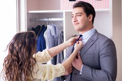 The wife helping husband to get dressed up. Wife helping husband to get dressed up Stock Photo