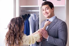 The wife helping husband to get dressed up. Wife helping husband to get dressed up Stock Images